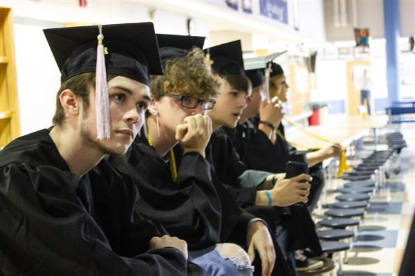 Seniors sitting in a row with cap and gowns
