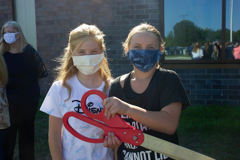 Two girls holding giant scissors